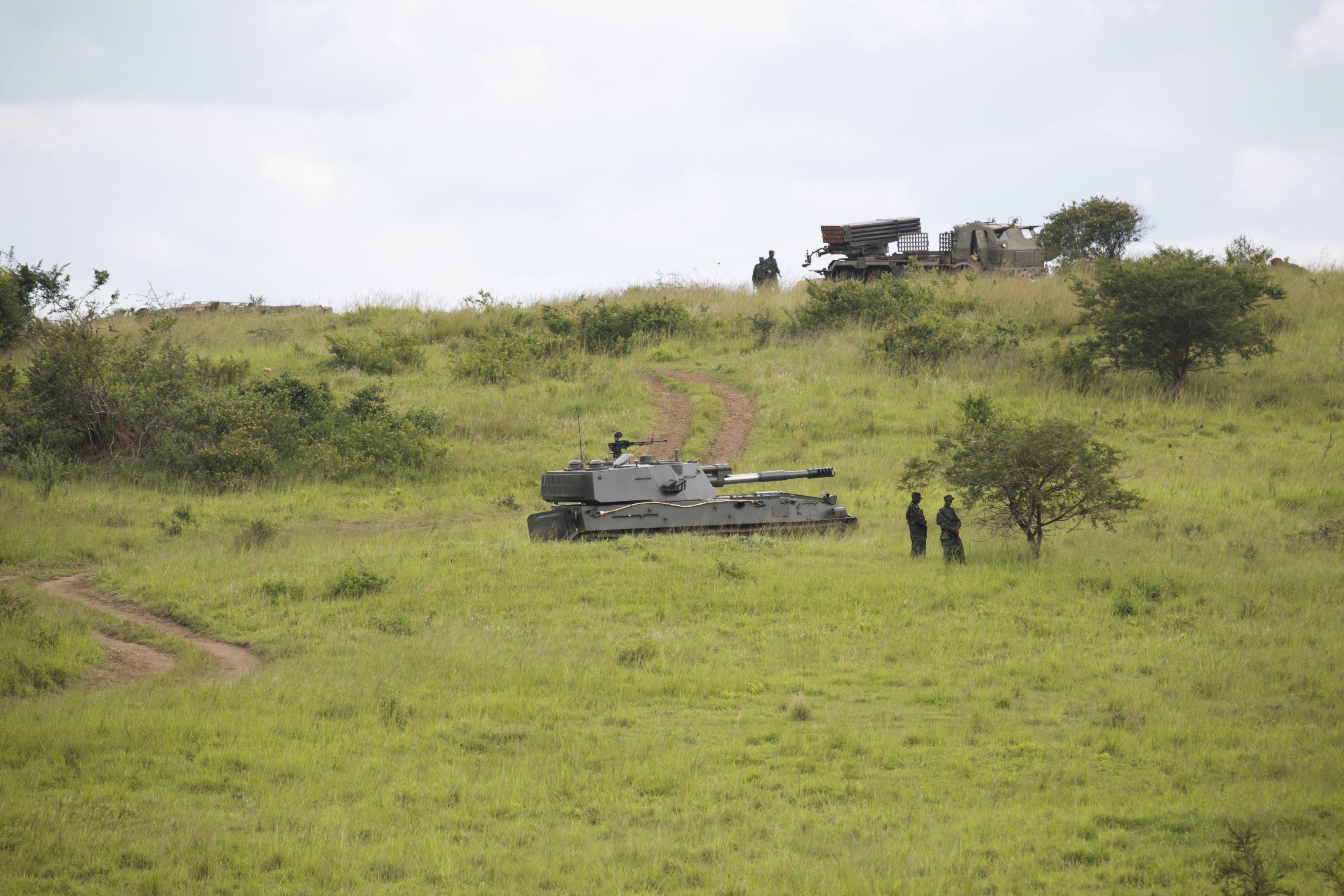 """122-мм самоходная гаубица SН3 китайского производства вооруженных сил Руанды во время показательных учений """"Hard Punch II"""". На заднем плане видна боевая машина 122-мм РСЗО RM-70 чехословацкого производства (пять систем были приобретены Руандой в Словакии в 1997 году). Габиро (Руанда), 10.11.2017."""