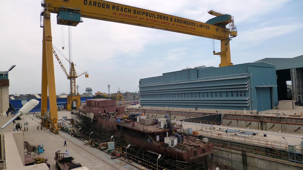 250-тонный главный козловый подъемный кран Goliath индийского судостроительного предприятия Garden Reach Shipbuilders & Engineers (GRSE) до обрушения. Видны оба сухих строительных дока (еще без частичного перекрытия) и корпусный цех (справа). Снимок предположительно 2012 года.
