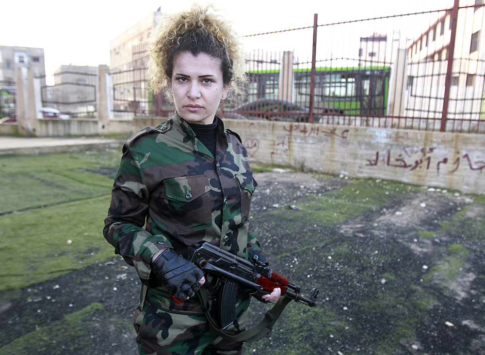 A new member of Syria's National Defense Force holds her rifle at a training center in Homs. (Anwar Amro — AFP/Getty Images).