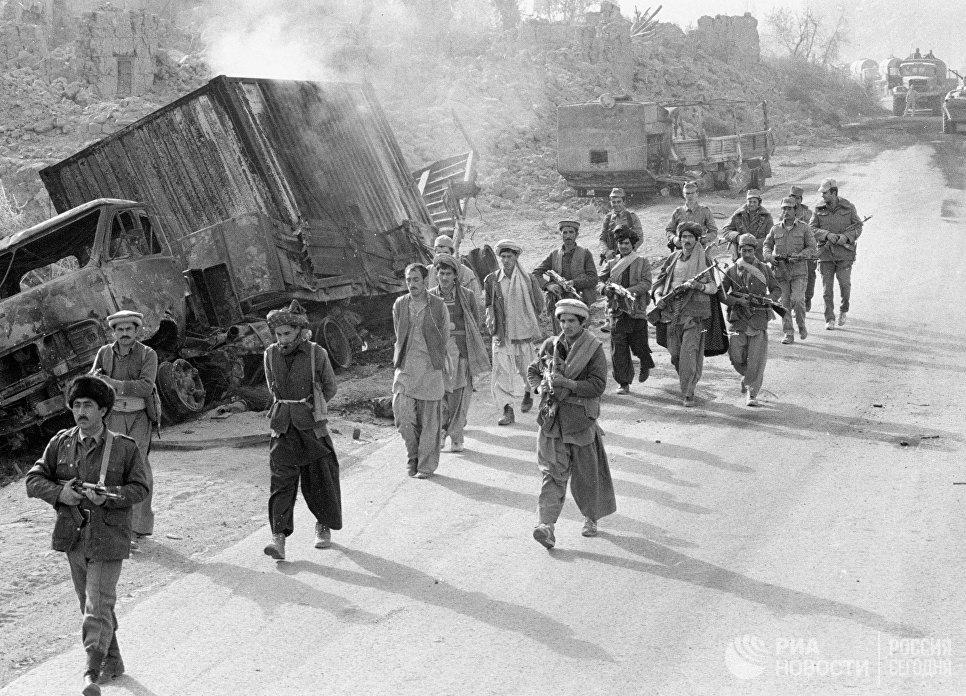 Бойцы народной милиции Афганистана и советские военнослужащие конвоируют захваченных в плен моджахедов. 1985 год.