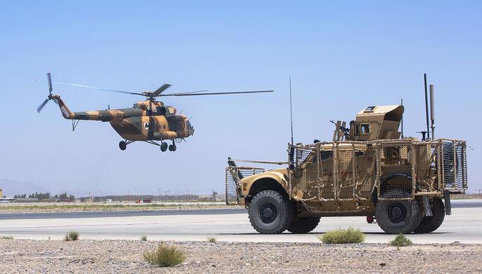 Вертолет национальной армии Афганистана и бронемашина ВС США на авиабазе в Кандагаре.