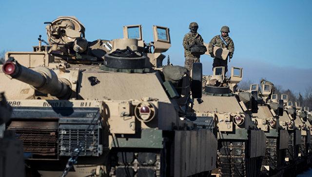 Американские военные готовят танки Абрамс к разгрузке на железнодорожной станции в Литве.