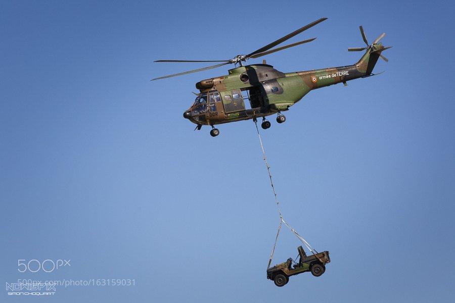 Вертолет Aérospatiale AS.332 Super Puma армейской авиации Франции с легким тактическим автомобилем Peugeot P4 на внешней подвеске.