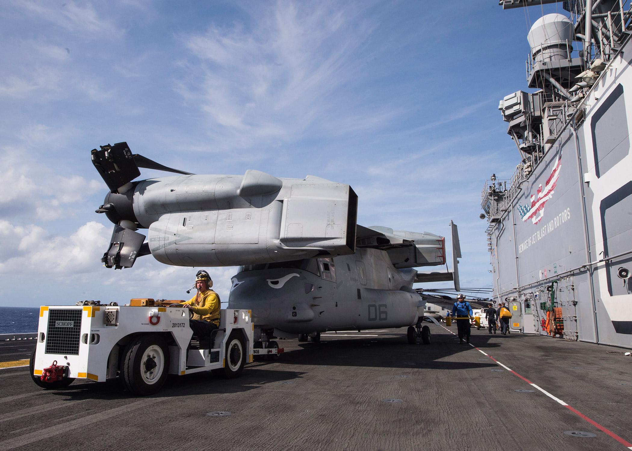 Младший офицер 3-го класса Вилли Кросон буксирует конвертоплан MV-22 Osprey на летной палубе десантного корабля USS Makin Island (LHD 8). (Фото: ВМС США).