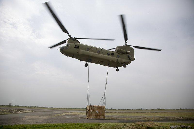 Вертолет CH-47 Chinook из целевой группы «Железные рыцари» осуществляет подъем груза на внешней подвеске во время операции воздушных перевозок в международном аэропорту Робертс 12-го декабря 2014-го года. (Фото сержанта 1-го класса Брайена Ворхиса (Brien Vorhees), Армия США).