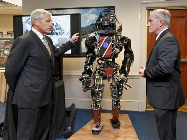 Министр обороны США Чак Хейгел вместе с представителем DARPA Брэдом Таусли осматривает новейшие разработки агентства перед уходом с поста в 2015 году .