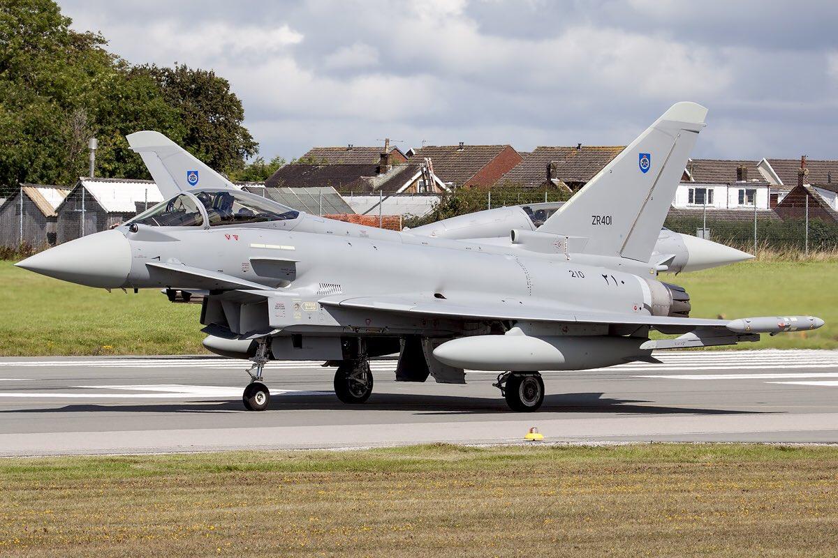 """Вторая партия истребителей Eurofighter Typhoon, построенных на британской производственной линии корпорации BAE Systems для Омана, перед вылетом из Вартона (Великобритания) в Оман. На переднем плане первый построенный для Омана одноместный истребитель с бортовым номером """"210"""" (серийный номер NS001, временный британский военный номер ZR401), на заднем плане третий двухместный истребитель с бортовым номером """"202"""" (серийный номер NT003, временный британский военный номер ZR412). 07.08.2017."""