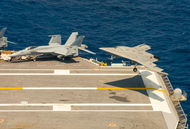 Палубный беспилотник X-47B и истребитель F/A-18 Hornet на палубе авианосца «Теодор Рузвельт». 17 августа 2014 года.