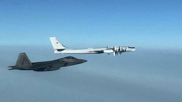 Истребитель F-22 командования воздушно-космической обороны США и российский бомбардировщик Ту-95 в небе у берегов Аляски