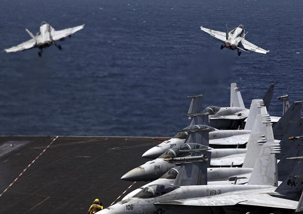 Истребители США F/A-18 взлетают с палубы авианосца США USS George H.W. Bush в Персидском заливе.
