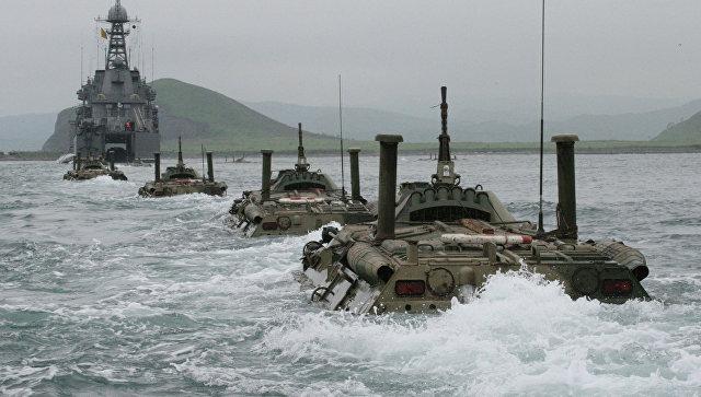 Колонна бронетранспортеров идет к большому десантному кораблю с целью погрузки на него на учениях морской пехоты Тихоокеанского флот.
