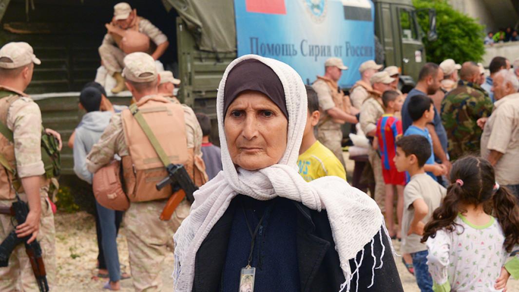 Местная жительница в очереди на раздачу гуманитарной помощи российскимивоенные из Центра примирения враждующих сторон жителям деревни Мшейрфа в провинции Латакия.
