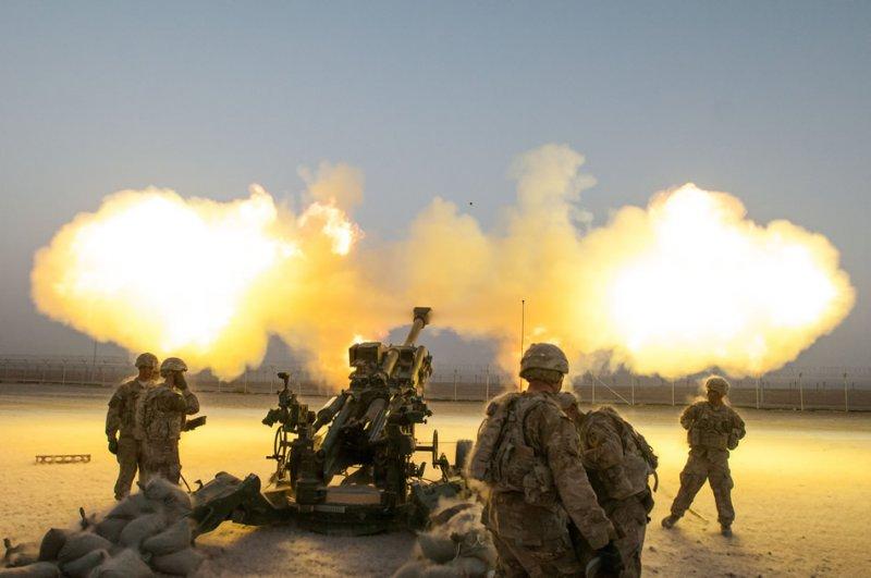 Американские солдаты батареи Альфа 2-го батальона 77-го полка полевой артиллерии 4-й пехотной бригадной боевой тактической группы 4-й пехотной дивизии ведут артиллерийский огонь из 155-мм буксируемой гаубицы M777A2 22-го августа 2014-го года на аэродроме в Кандагаре в Афганистане. Солдаты и их подразделение проводят пристрелочную стрельбу. (Фото специалиста Ариэля Соломона (Ariel Solomon), Армия США).