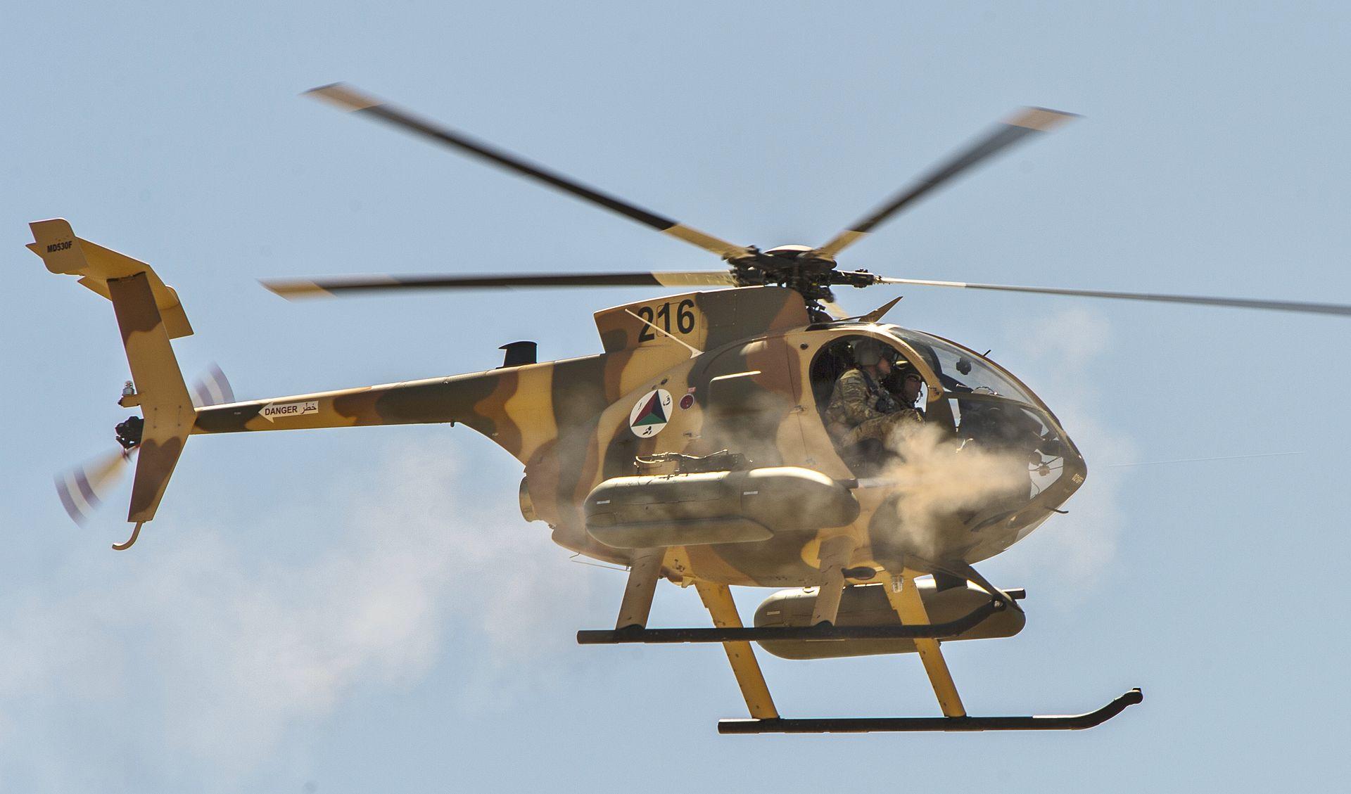 Легкий боевой вертолет MD Helicopters MD-530F Cayuse Warrior ВВС Афганистана ведет огонь из подвесных 12,7-мм пулеметных контейнеров FN M3P во время публичной демонстрации близ Кабула, 09.04.2015.