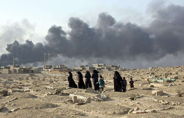 Семья на разрушенном кладбище в Катаре, 50 км от Мосула, Ирак, 27 октября 2016 года.