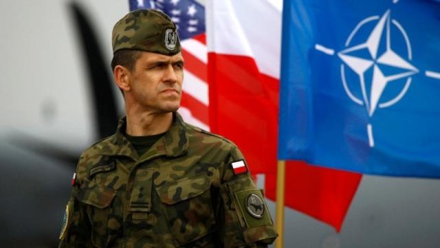 Польский военнослужащий на фоне флагов Польши, США и НАТО