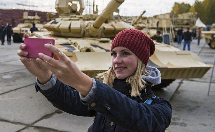 Посетитель фотографируется на фоне танка Т-90А на 10-й международной выставке Russia Arms Expo.