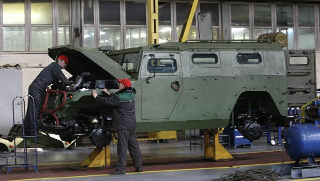 Рабочие осматривают бронеавтомобиль Тигр. Архивное фото.