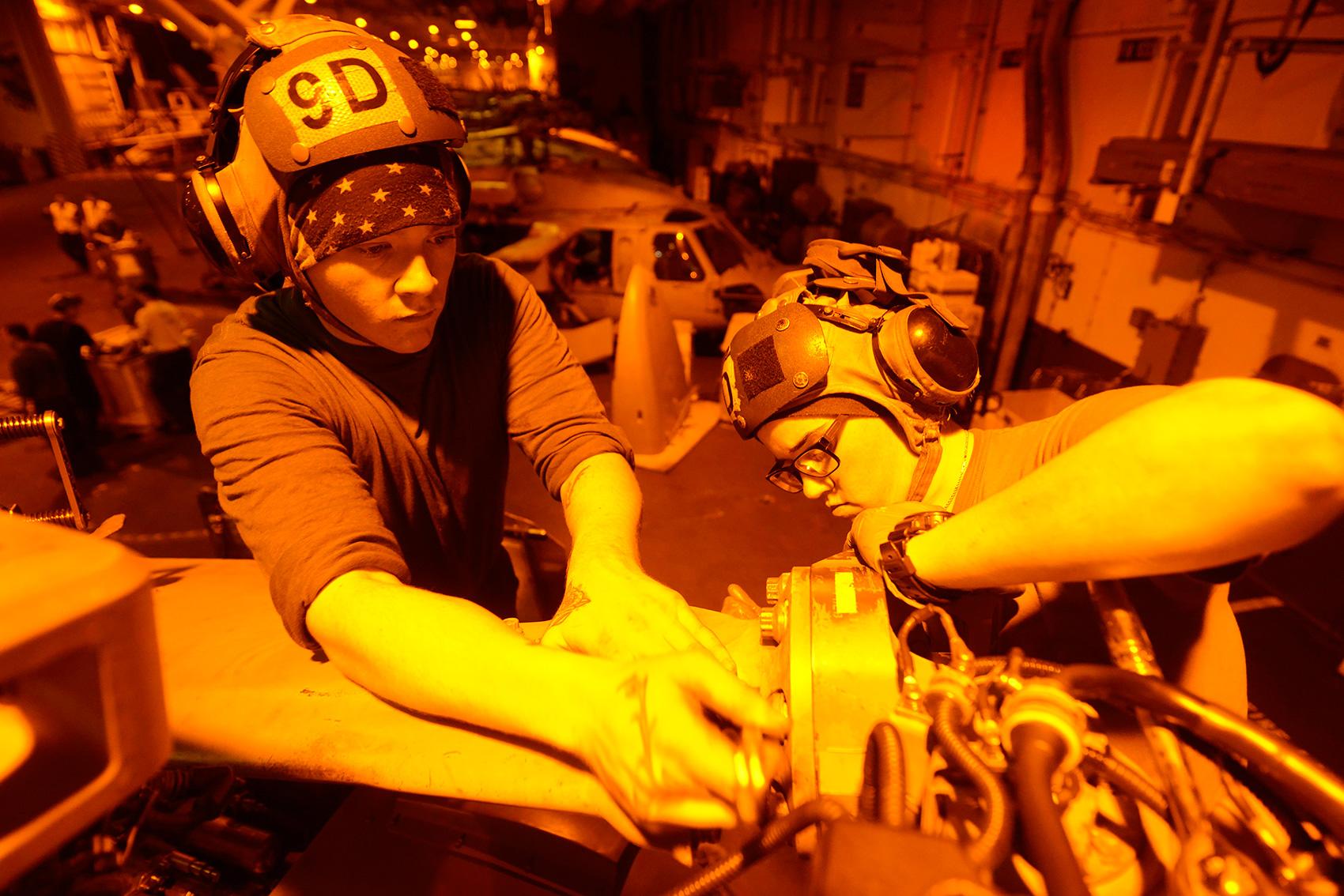 Помощник авиационного механика 3-го класса Ноа Уокер (слева) и помощник авиационного механика 2-го класса Эшли Тьон, служащие в Dragon Slayers Вертолетной морской боевой эскадрильи (HSC) 11, выполняют техническое обслуживание вертолета MH-60S Sea Hawk в закрытом ангаре авианосца класса Nimitz USS Harry S. Truman (CVN 75). (Фото: ВМС США).