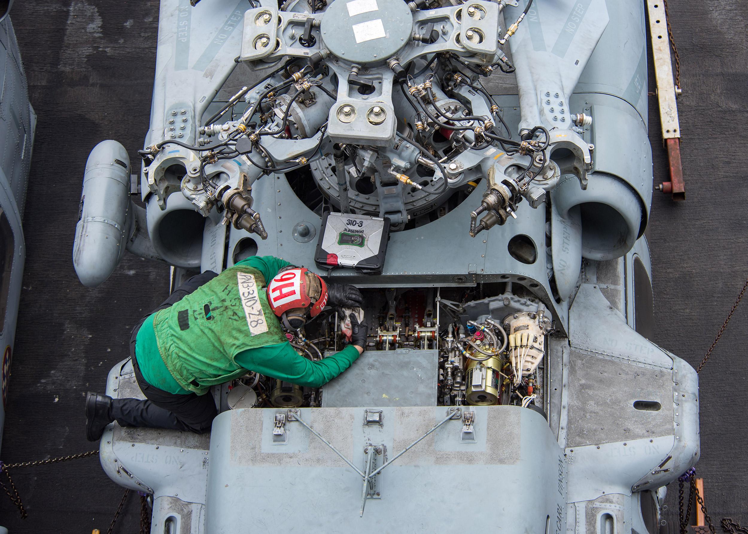 Служащий в Black Knights вертолетной боевой эскадрильи (HSC) 4 Сейлор, проводит техническое обслуживание вертолета MH-60S Sea Hawk на летной палубе авианосца класса Nimitz USS Carl Vinson (CVN 70). (Фото: ВМС США).