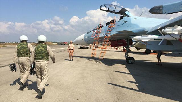 """Российские летчики готовятся к посадке в истребитель Су-30 перед вылетом с аэродрома """"Хмеймим"""" в Сирии"""