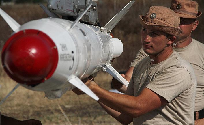 """Российские военные подвешивают высокоточную ракету Х-25 к самолету Су-24 на авиабазе """"Хмеймим"""" в Сирии."""