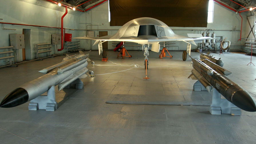 """Полноразмерный макет боевого беспилотного летательного аппарата """"Скат"""" (на заднем плане)."""
