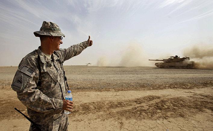 Солдат армии США дает знак экипажу танка М1А1 Abrams во время учений в Ираке.