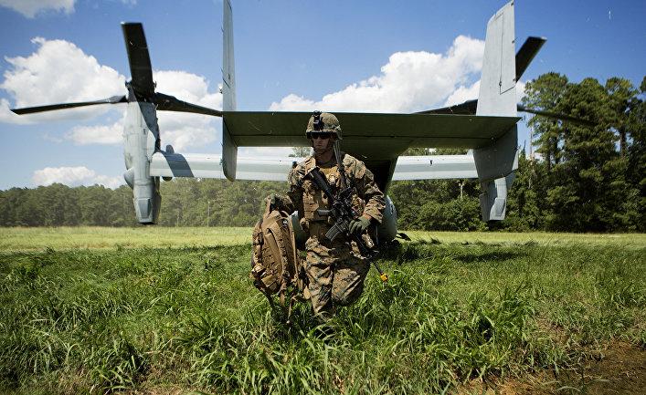 Солдат Корпуса морской пехоты США выходит из конвертоплана MV-22 Osprey.