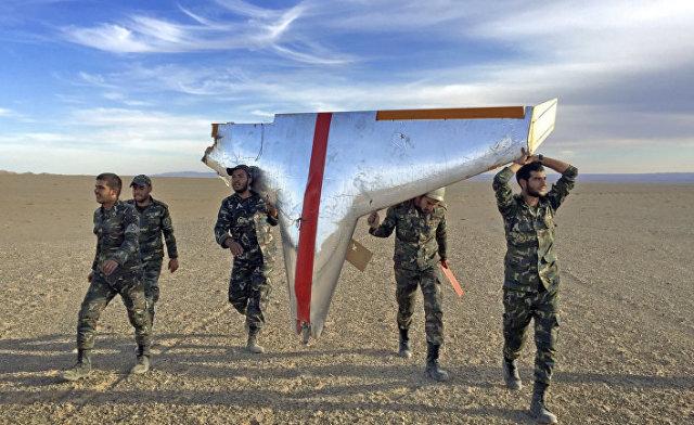 Солдаты вооруженных сил Ирана несут обломки беспилотника