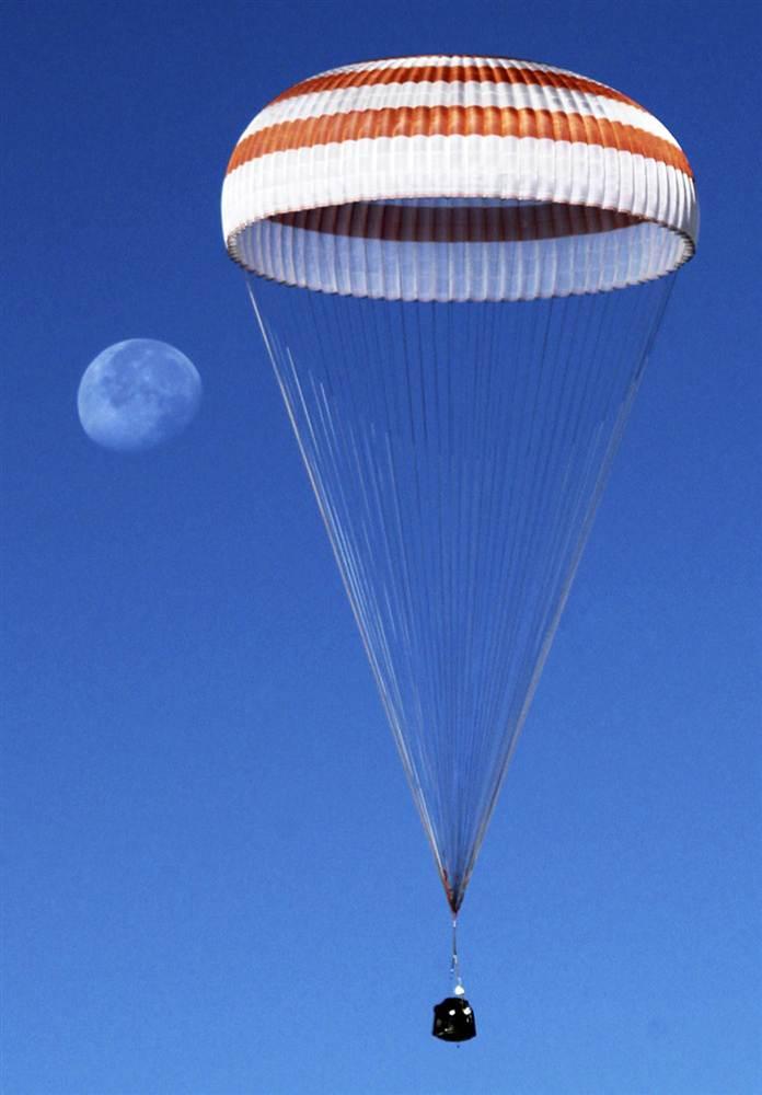 Луна виднеется в небе рядом с куполом парашюта, на котором спускают капсулу космического корабля «Союз», 16 сентября 2011 года, Казахстан. Внутри капсулы находятся два российских космонавта и астронавт НАСА, возвращающиеся на Землю после пребывания на борту МКС.