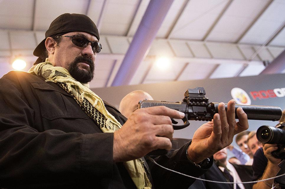 """Знаменитый американский актер Стивен Сигал с самозарядным пистолетом Сердюкова с глушителем во время посещения международной выставки """"Оборонэкспо-2014""""."""
