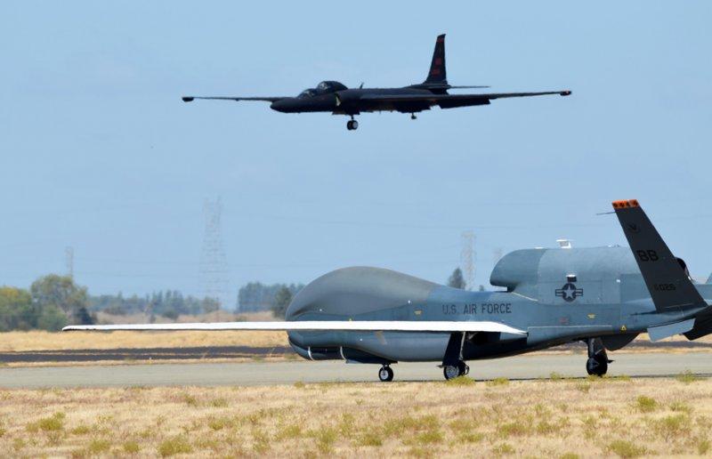БПЛА RQ-4 Global Hawk готовится к взлету в то время как разведчик U-2 заходит на посадку 17-го сентября 2013-го года на авиабазе Бил, штат Калифорния.
