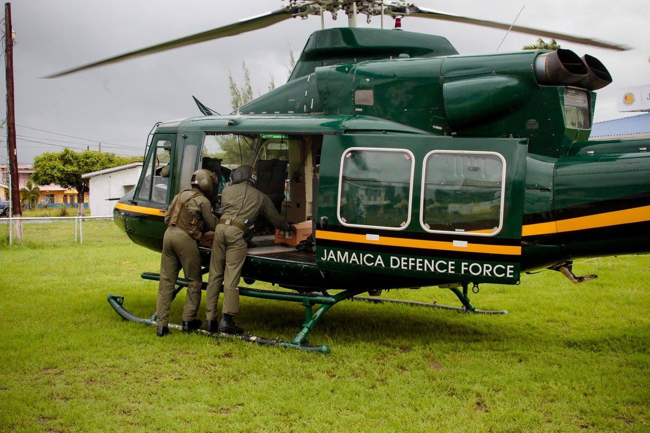 Вертолет Bell 412 авиационного крыла Сил обороны Ямайки во время оказания гуманитарной помощи пострадавшим от наводения жителям одного из глубинных районов острова, 16.05.2017.