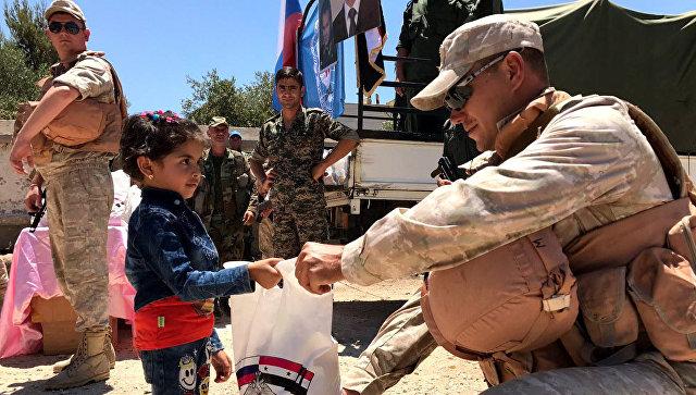 Военнослужащие российского центра по примирению враждующих сторон раздают гуманитарную помощь в сирийской провинции Кунейтра.