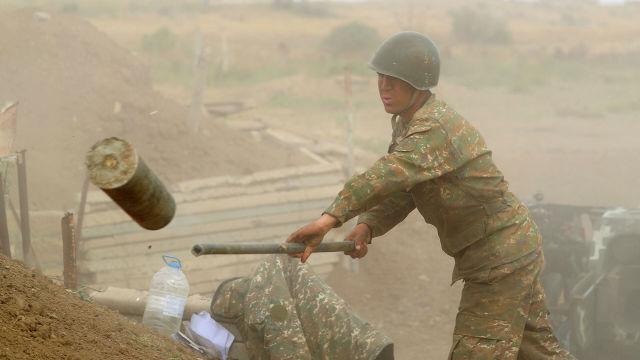 Военнослужащий стреляет из пушки по позициям вооруженных сил Азербайджана на линии соприкосновения в Нагорном Карабахе