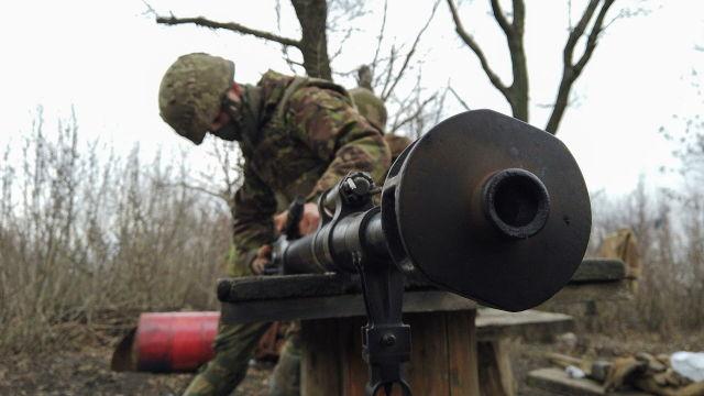 Военнослужащий украинских вооруженных сил чистит оружие на боевых позициях на линии разделения возле города Донецк