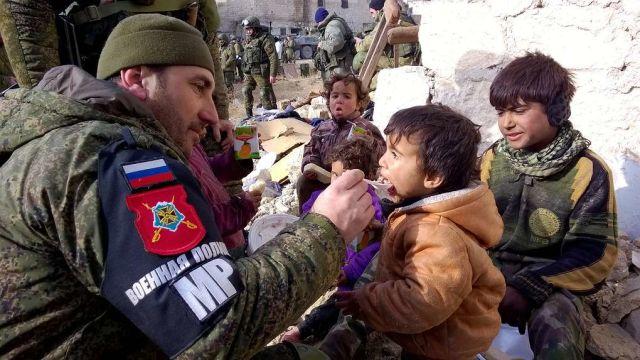 Военнослужащий российской военной полиции кормит сирийских детей в районе Аль-Миасар, декабрь 2016 год