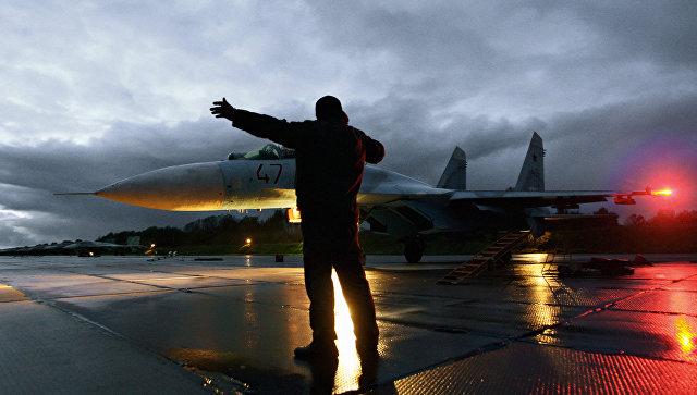 Военный техник дает отмашку на взлет истребителя Су-27. Архивное фото.