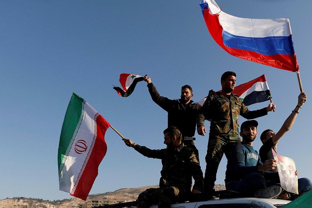 Сирийцы с иранскими, российскими и сирийскими флагами протестуют против воздушных ударов США и их союзников по Дамаску.