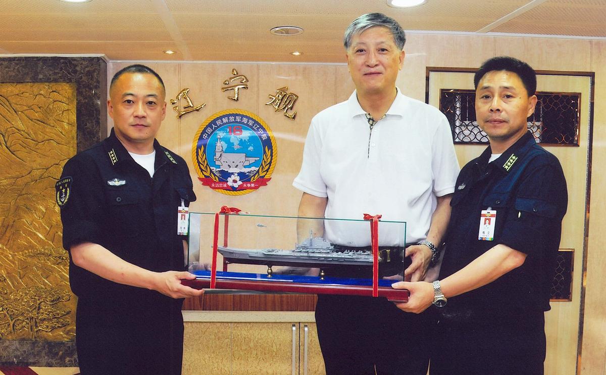 Гонконгский бизнесмен Сюй Чженпинь (Xu Zengping) и два офицера ВМФ НОАК держат в руках модель авианосца «Варяг».