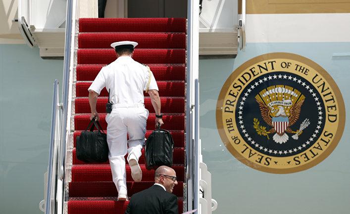 """Представитель военно-морского флота США заносит """"ядерный чемоданчик президента"""" на борт президентского самолета."""