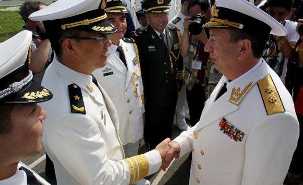 Заместитель главнокомандующего ВМФ РФ вице-адмирал Александр Федотенков (справа) пожимает руку офицеру Военно-морских сил Китая на торжественной встре