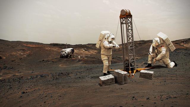 Занимающиеся бурением в исследовательских целях астронавты на Марсе в представлении художника